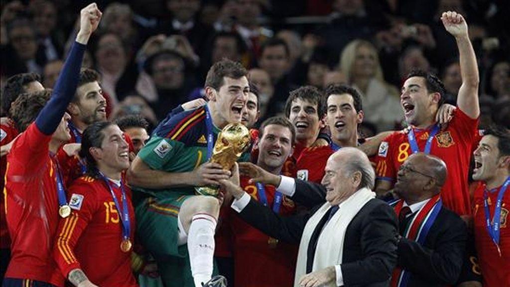 El capitan de la selección española de fútbol, Iker Casillas,iz. recibe del presidente de la FIFA, Josep Blatter,d, la copa del Mundial de Sudáfrica que la selección española consiguió tras vencer en la final a la selección de Holanda por 1-0 EFE