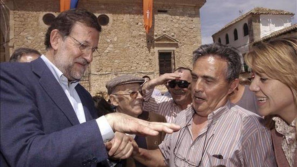 El presidente del Partido Popular, Mariano Rajoy (i), junto a la presidenta del PP de Castilla-La Mancha y secretaria general nacional, María Dolores Cospedal (d), saluda a un grupo de vecinos a su llegada a la localidad toledana de El Toboso. EFE