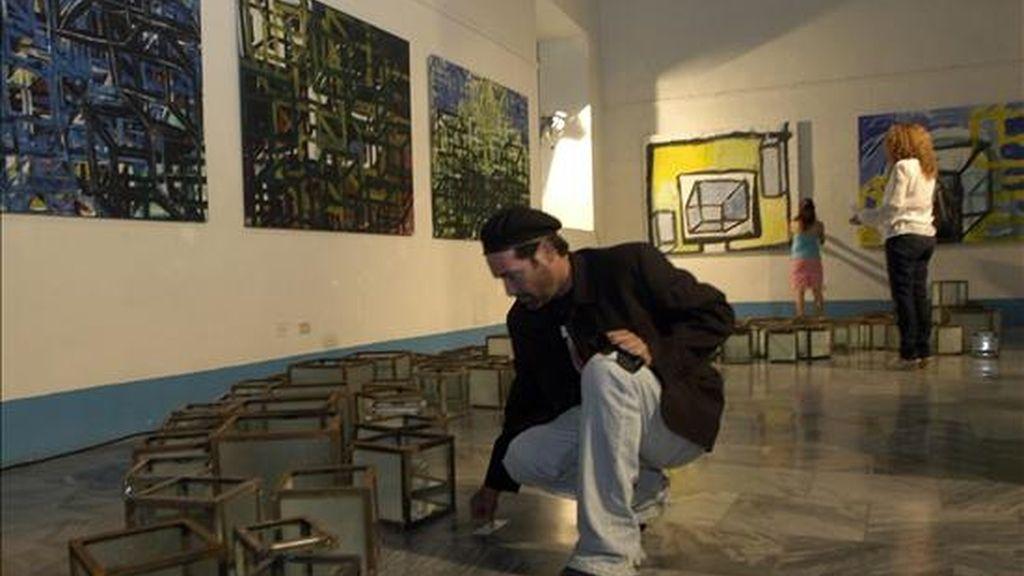 El actor cubano Jorge Perugorría (c) arregla varios objetos en el local donde se exponen algunas de sus obras. EFE/Archivo