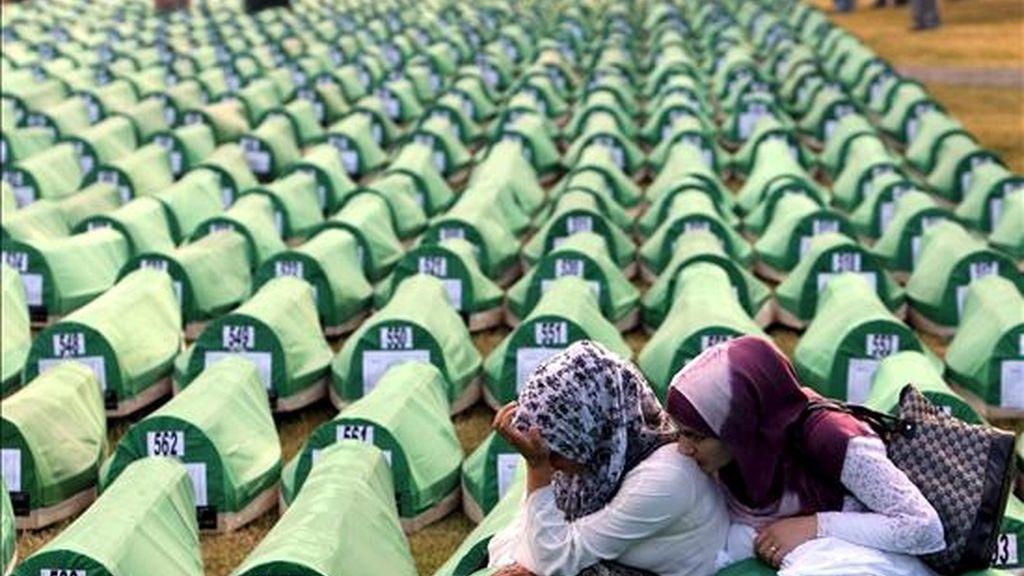Dos mujeres lloran entre féretros durante el funeral de 775 víctimas de la matanza de Srebrenica recientemente identificadas, en el memorial de Potocari, cerca de Srebrenica (Bosnia). Hoy se conmemora el decimoquinto aniversario de la matanza de unos 8.000 varones musulmanes, ocurrida en 1995 tras la conquista de ese antiguo enclave oriental musulmán por las tropas serbobosnias del general Ratko Mladic, aún prófugo de la Justicia. EFE