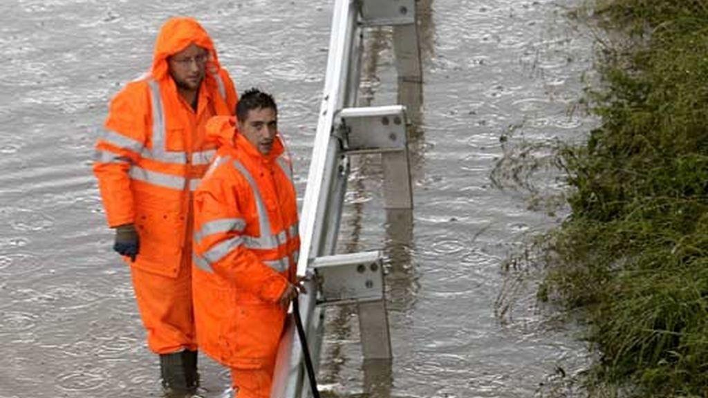 Dos operarios de la Diputación de Vizcaya intentan aliviar de agua en la carretera N-637, a su paso por la localidad vizcaína de Berango. Foto: EFE