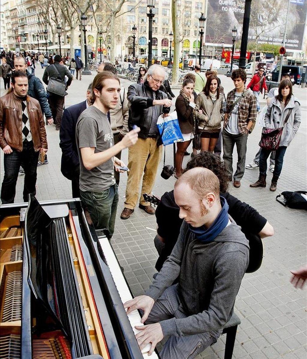 """Un peatón toca una melodía en un piano de cola instalado en la Plaza de Cataluña, uno de los varios instalados por el centro de la ciudad por la organización del concurso Maria Canals con el lema que tiene grabado sobre el teclado, """"Siéntate. Estoy en tus manos"""", dispuesto para dejarse tocar por todo aquel que se atreva para el deleite de los viandantes. EFE"""