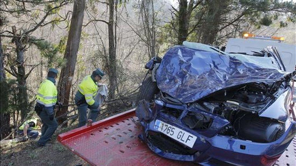 Dos guardias civiles pasan junto a un vehículo que accidentado en la localidad coruñesa de Toques el pasado 22 de marzo. EFE/Archivo