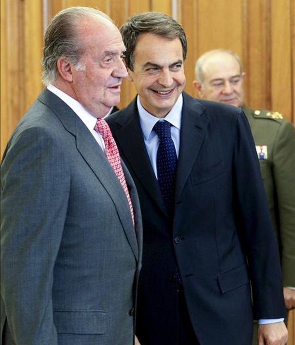 El rey Juan Carlos conversa con el presidente del Gobierno, José Luis Rodríguez Zapatero (d), durante el acto en el que los nuevos ministros prometieron sus cargos, en el Palacio de la Zarzuela. EFE/Archivo