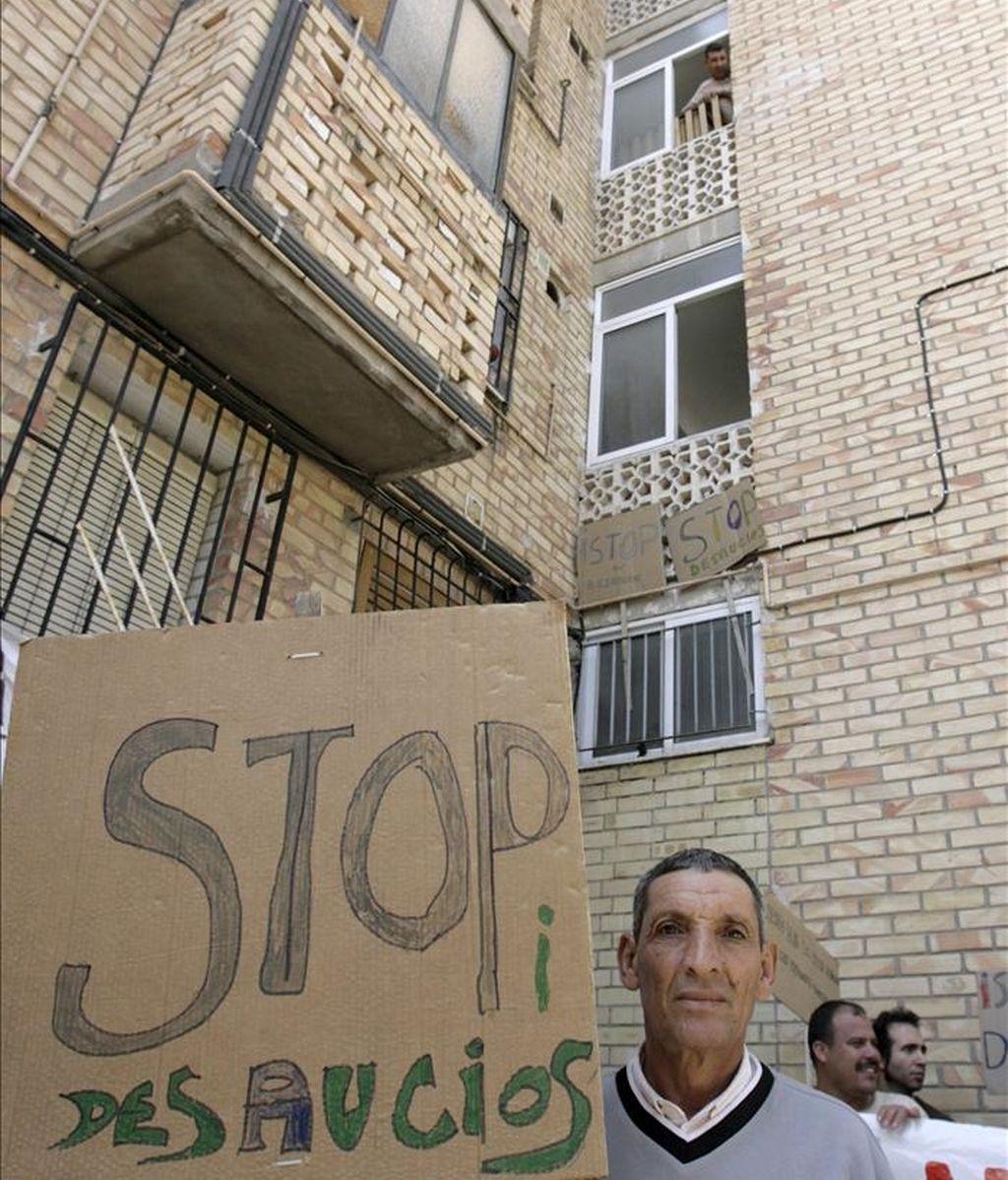Vecinos y miembros de la Plataforma de Afectados por las Hipotecas de El Palmar ante la vivienda de Rabah Maizi, el joven de 32 años que lleva diez en España, donde vino procedente de Marruecos en busca de trabajo, en el barrio de Los Rosales de Murcia, donde han impedido el desalojo de Maizi y su familia. EFE