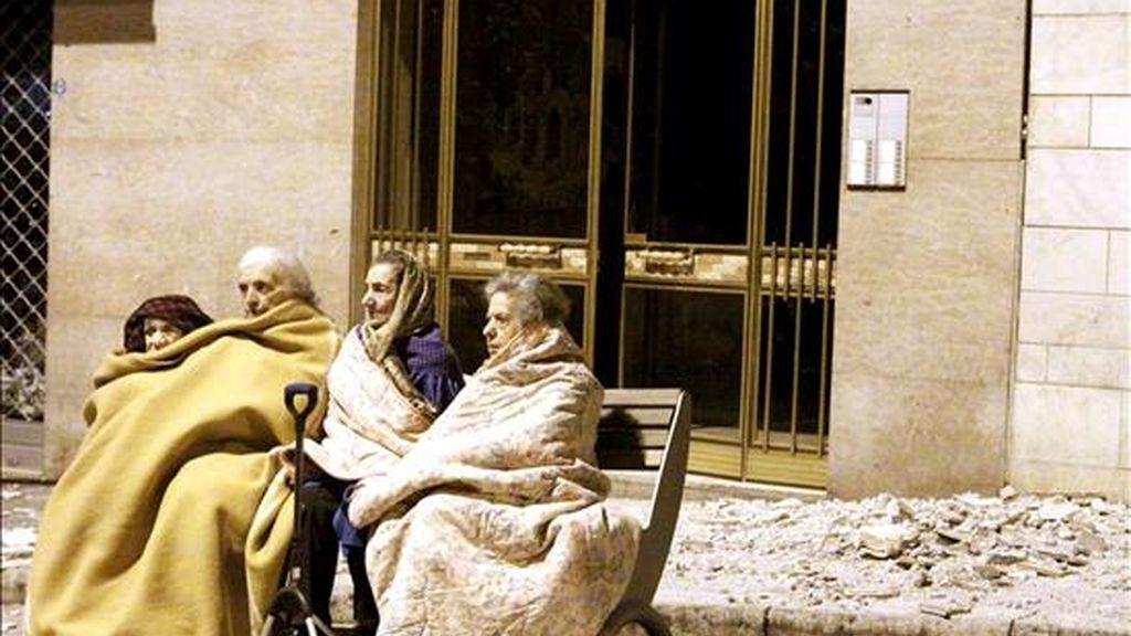 Cuatro ancianas sentadas en el banco de una calle junto a los escombros provocados por el terremoto de hoy de 5,8 grados de magnitud en la escala de Richter que sacudió el centro de Italia durante la madrugada, en L'Aquila. EFE