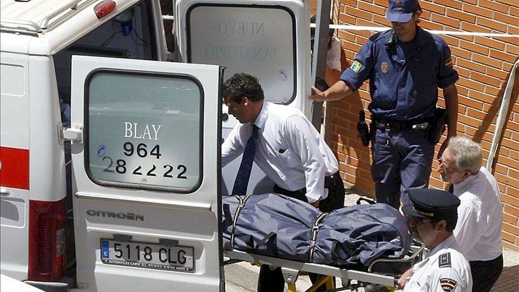 Empleados de los servicios funerarios, junto a agentes de las Fuerzas de Seguridad, retiran el cadáver de la mujer de 36 años que falleció en mayo de 2009 asfixiada en Castellón a manos de su compañero sentimental, quien le han condenado a 20 años de cácerl. EFE/Archivo
