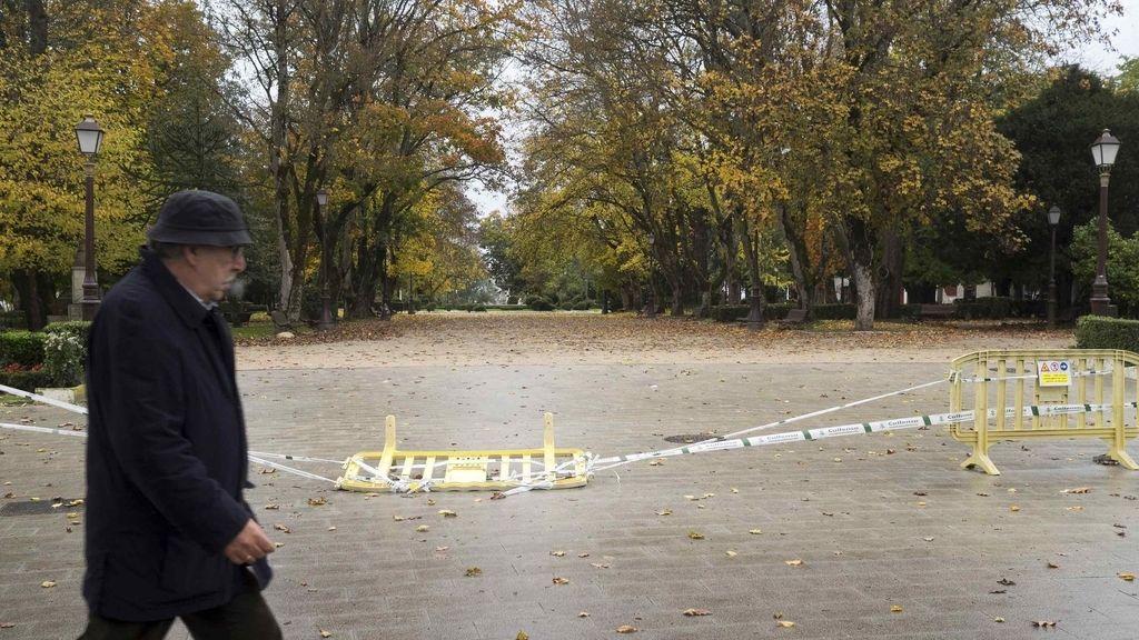 Un hombre camina por el exterior del Parque Rosalía de Castro, en Lugo, que se ha mantenido cerrado a causa de las fuertes rachas de viento previstas