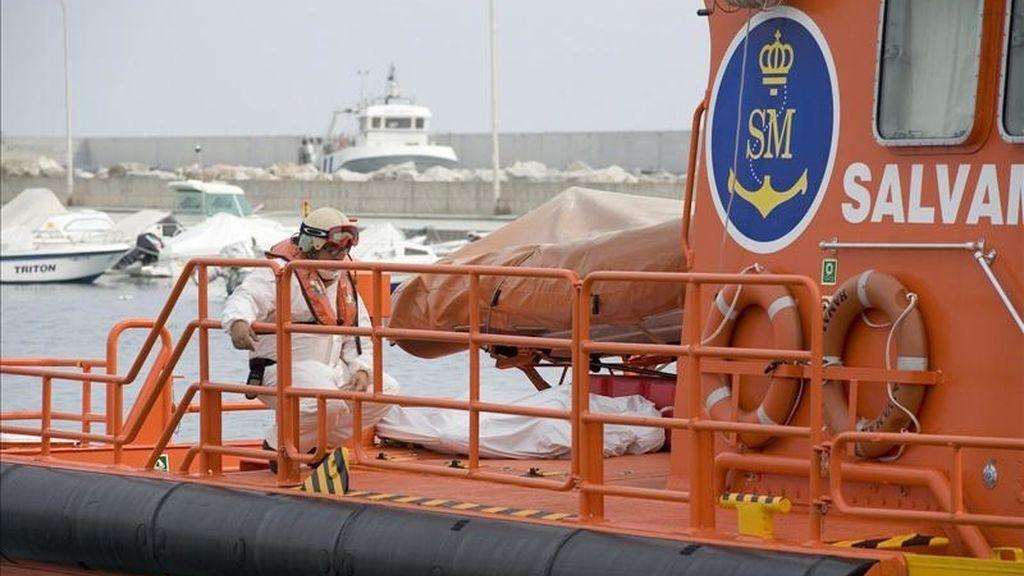 Un miembro de Salvamento Marítimo junto a los cadáveres de un varón y de dos menores, un niño de unos 3 años y una niña de 1 año, recuperados durante la búsqueda de una patera semihundida al sur de Adra. EFE