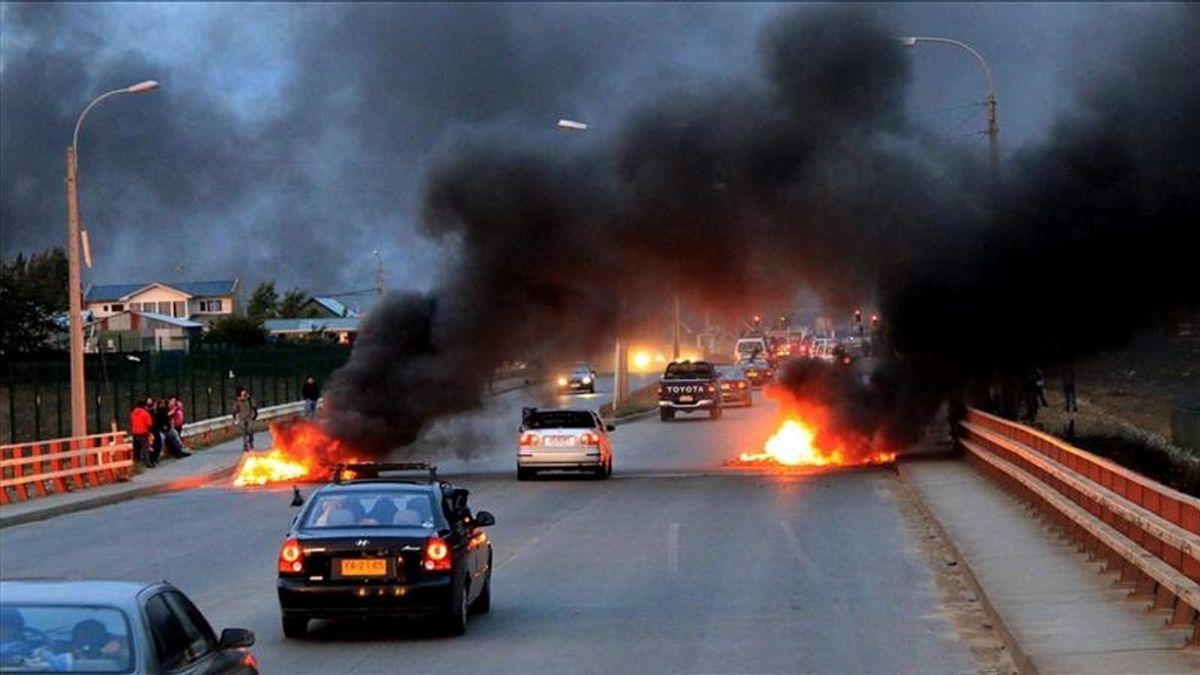 Manifestantes queman neumáticos este miércoles en una calle de Punta Arenas (Chile). Tras la decisión del Gobierno de subir en un 16,8% el precio del gas en Magallanes, única región chilena productora de este combustible, la comunidad local se movilizó a través de la Asamblea Ciudadana, que convocó a un paro indefinido. EFE