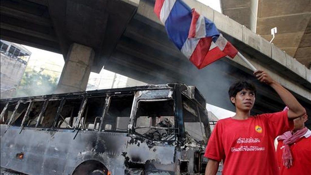 Un autobús calcinado bloquea hoy una calle del centro de Bangkok. EFE
