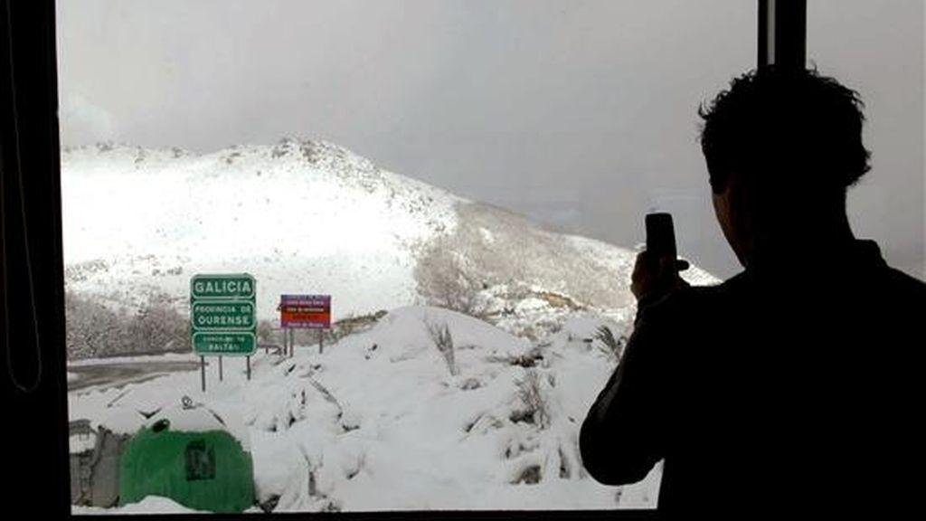 Un joven fotografía el paisaje de nieve desde el interior de un restaurante situado en la frontera entre Baltar (Ourense) y Montealegre (Portugal), a pocos metros del cartel que anuncia la entrada en Galicia. EFE
