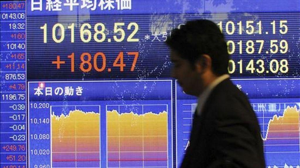 Un hombre pasa por delante de una pantalla que refleja eL índice Nikkei de la Bolsa de Valores de Tokio. EFE/Archivo