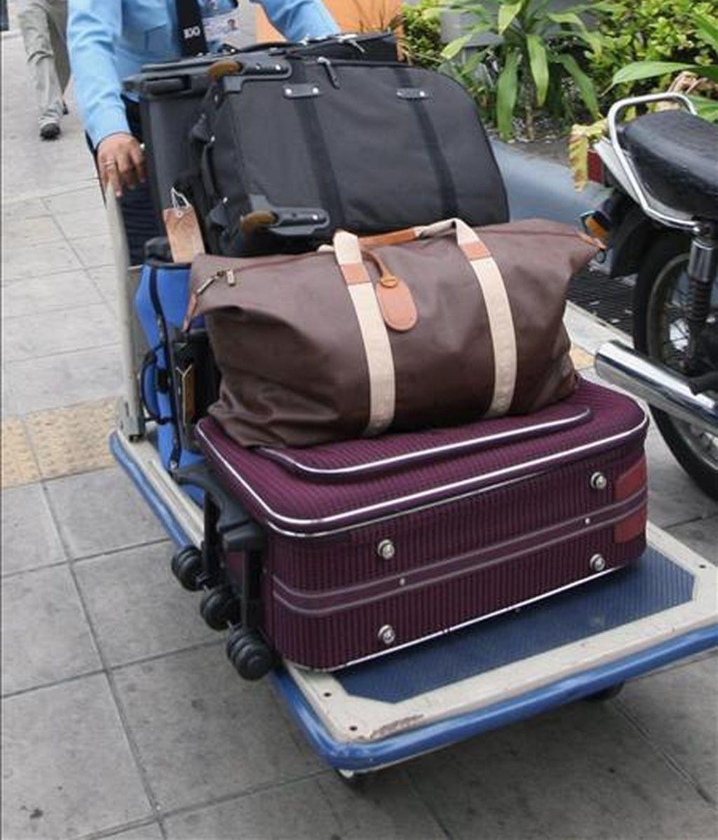 Un empleado de un hotel empuja un carrito lleno de maletas. EFE/Archivo