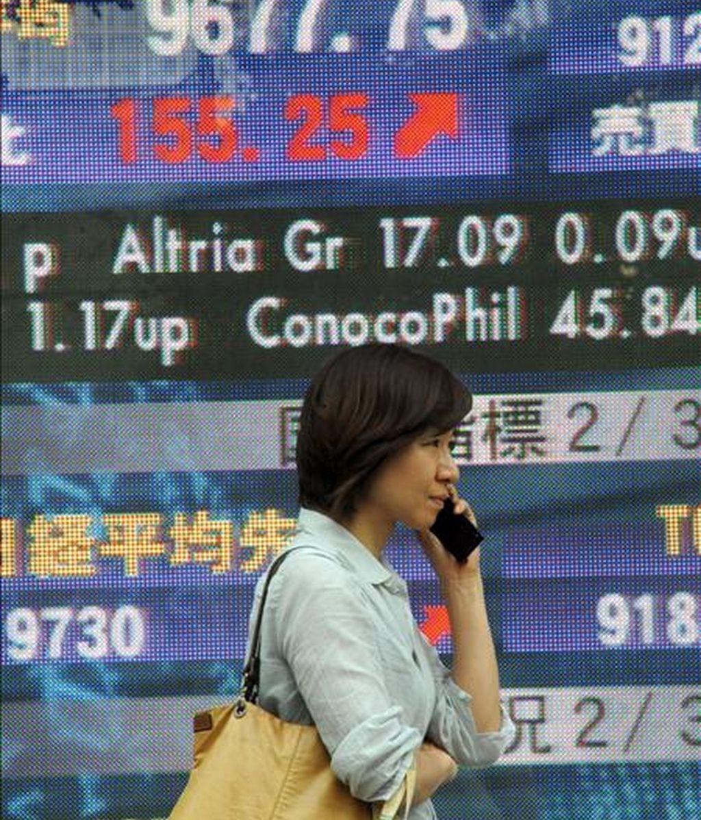 Un peatón pasa por delante de una pantalla electrónico con el valor del índice Nikkei, en el centro de Tokio, Japón. EFE
