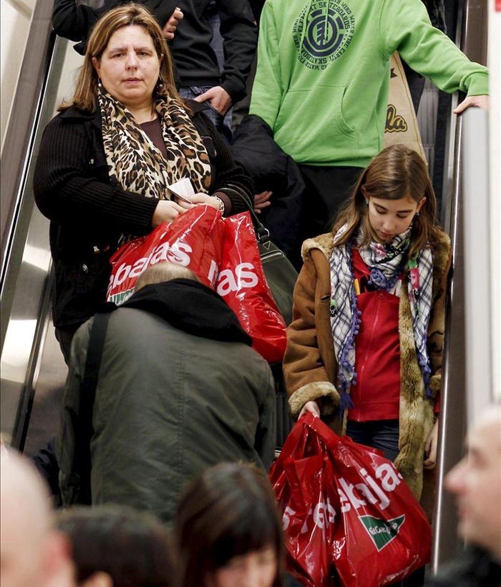Un grupo de personas descienden con sus compras por una escalera mecánica de una superficie comercial. EFE/Archivo