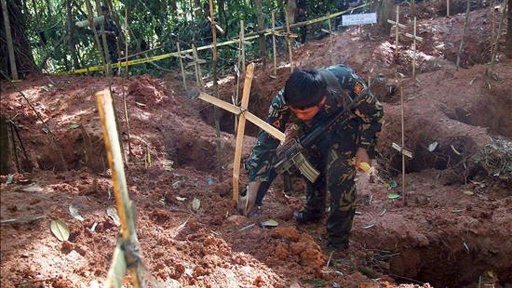 Fotografía de un soldado filipino ofreciendo una vela ante un fosa común con los restos que se cree pertenecen a soldados del Ejército de Nuevos Pueblos (NPA). EFE/Archivo