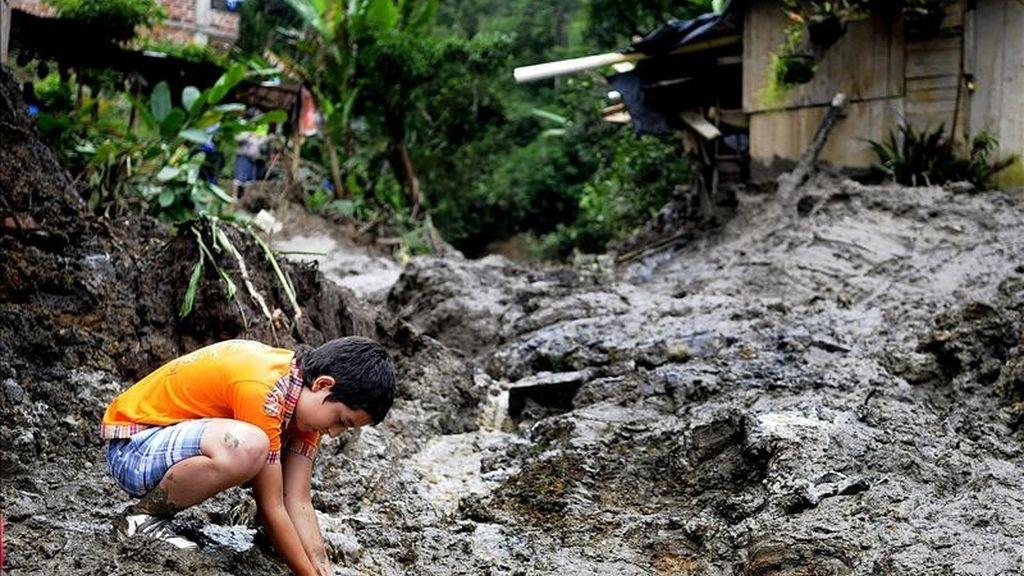 """Un niño juega en medio de un alud de tierra en el municipio de Sabaneta (Colombia). Los damnificados por las lluvias caídas en el país durante el último año superan ya los tres millones, una cifra """"histórica"""". EFE"""