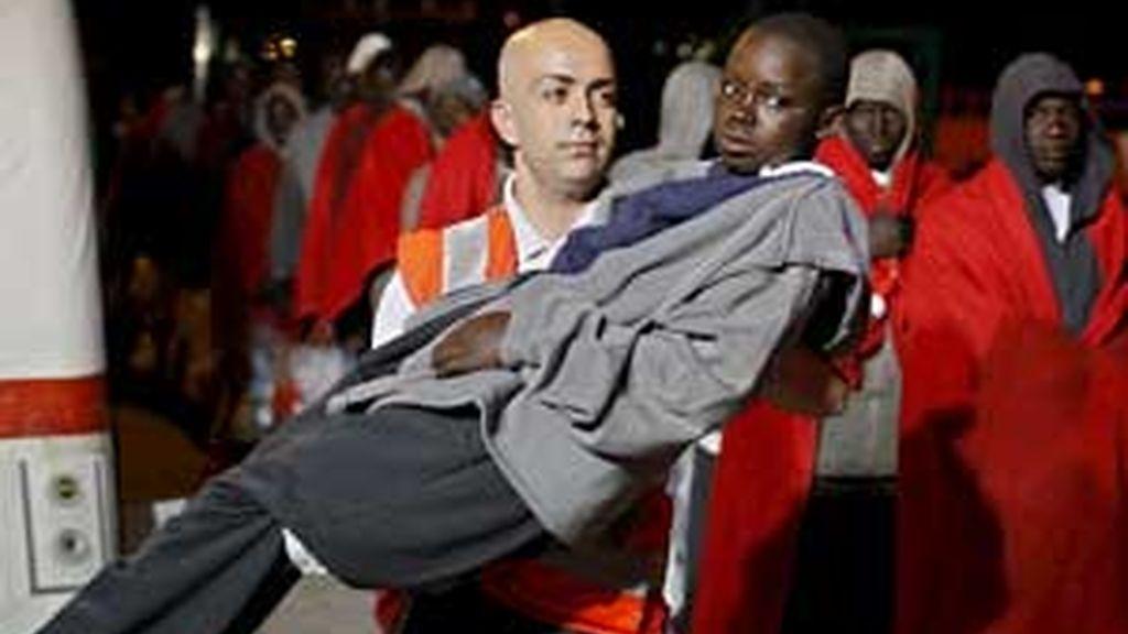 Un miembro de Cruz Roja traslada a uno de los 74 ocupantes del cayuco. Foto: EFE