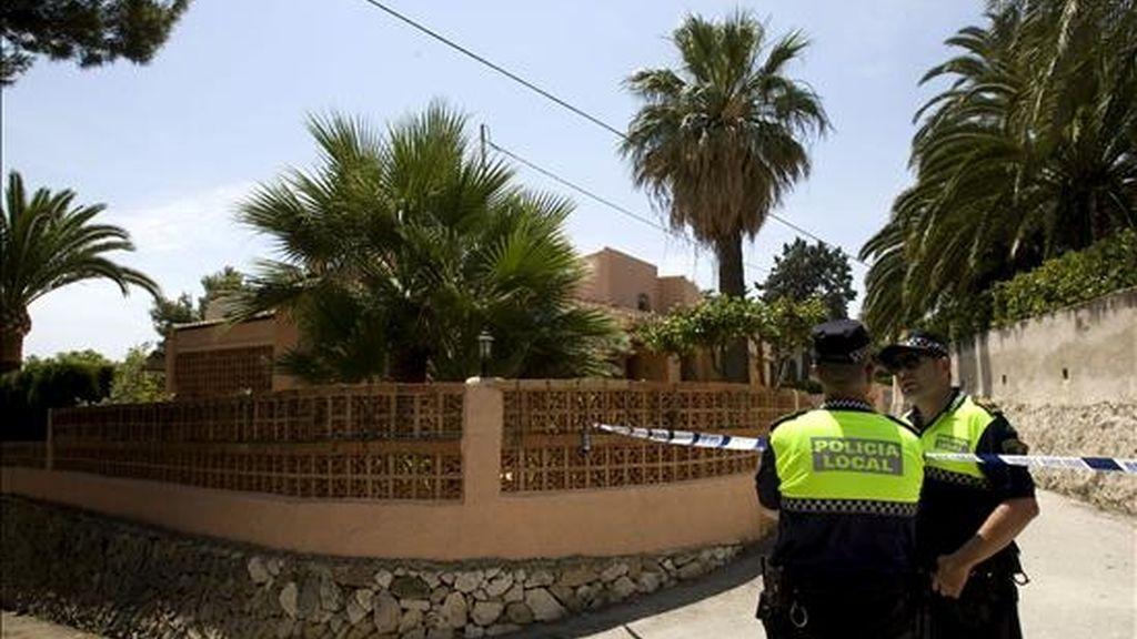 Dos policías municipales de Jávea (Alicante) controlan los accesos a la vivienda en la que un hombre de unos 30 años ha muerto tras ser agredido presuntamente por su compañero sentimental. EFE