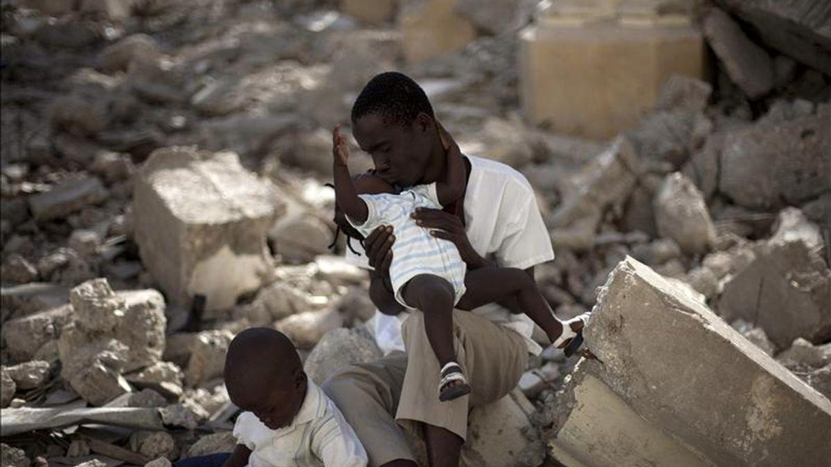 Un padre permanece con sus hijos durante una ceremonia religiosa en la catedral de Puerto Príncipe hoy, miércoles 12 de enero, día en que se conmemora el primer aniversario del terremoto que causó unos 300.000 muertos y dejó 1,2 millones de desplazados. EFE