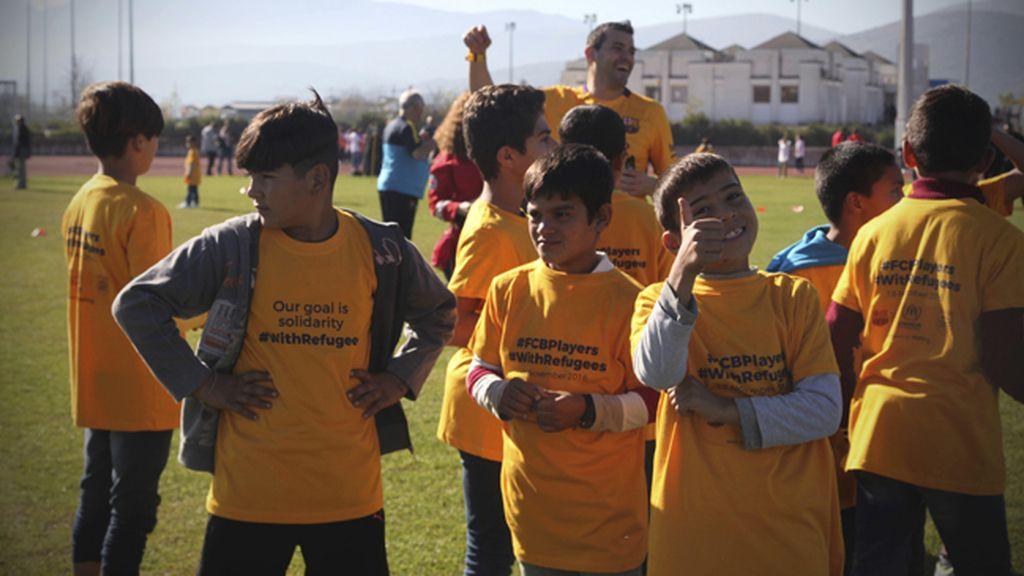 Veteranos del Barcelona visitan a niños refugiados en un acto solidario