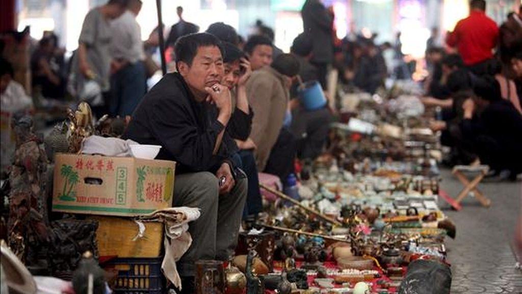 En la imagen, los vendedores de un mercado de Pekín, esperan la llegada de clientes hoy. EFE