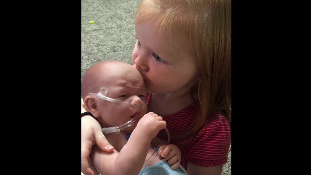 Nora con el muñeco que es igual que su hermano