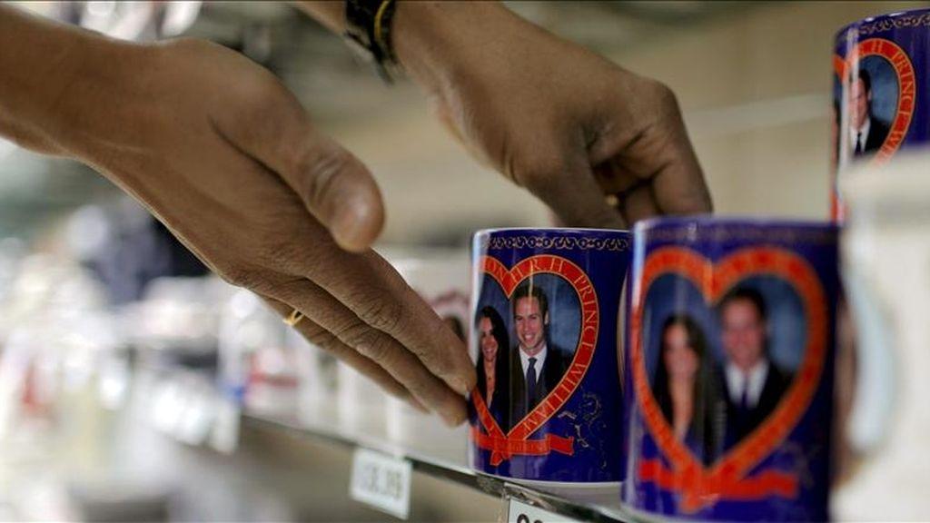 Una mujer ordena unas tazas que se venden como 'souvenirs' para conmemorar la Boda Real del príncipe Guillermo de Inglaterra con Kate Middleton, el próximo 29 de abril, en una tienda de Londres, Reino Unido. EFE/Archivo