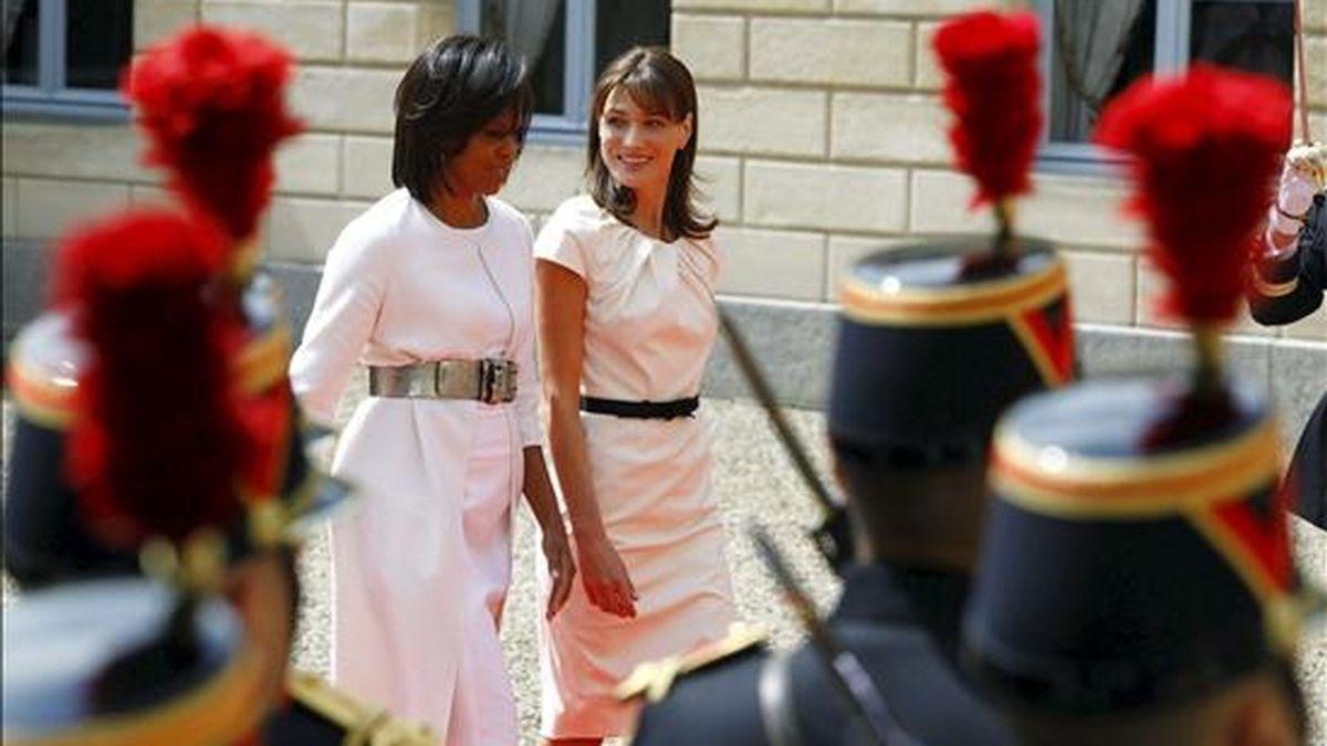 La primera dama francesa, Carla Bruni (dcha), camina junto a la primera dama estadounidense, Michelle Obama, hoy durante la celebración del 65 aniversario del Desembarco de Normandía en Caen, Normandía. EFE