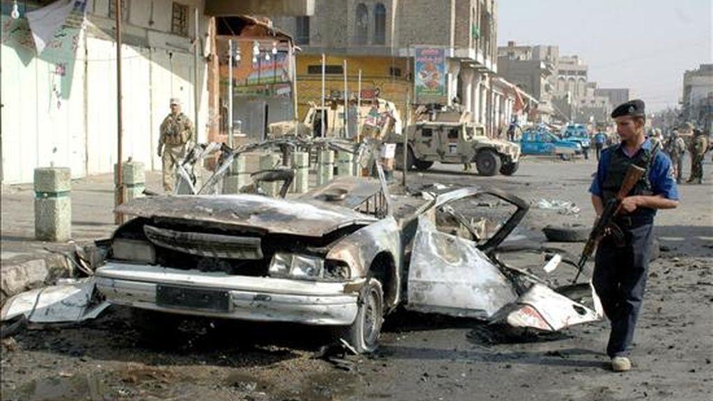 Policías iraquíes inspeccionan los restos de un vehículo utilizado hoy en un atentado con coche bomba en Bagdad. EFE