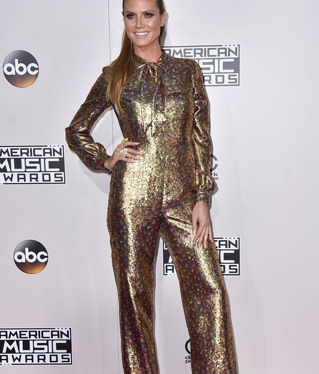 Heidi Klum apostó por los tonos dorados: mono estampado con lazada al cuello