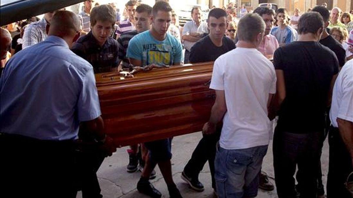 Varios jóvenes portan el féretro del joven de 20 años que ha fallecido en la localidad de Fuentesaúco (Zamora), al ser corneado por un toro en el encierro nocturno de las fiestas locales, a su llegada a la iglesia de San Juan Bautista, donde se ha oficiado el funeral. EFE