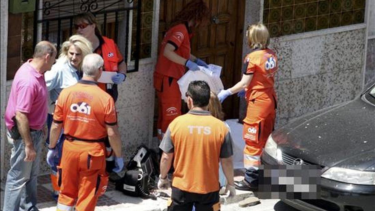 Miembros de los servicios sanitarios junto con el cadaver de la mujer que falleció en Pinos Puente (Granada) al ser golpeada en la cabeza con una azada. EFE/Archivo