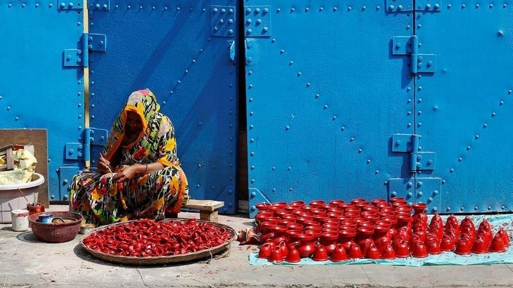 Mujer pintando lámparas de barro