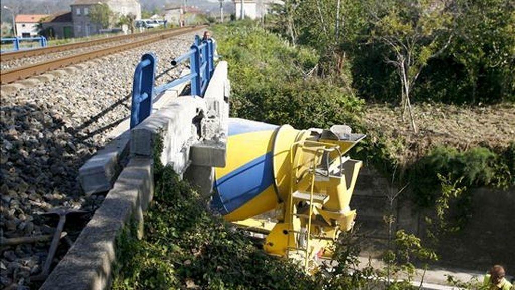 Vista de la hormigonera que ha quedado encajada en un puente y que arrancó las vigas, por el que discurre la línea ferroviaria Vigo-A Coruña, a la altura de la localidad de Alba (Pontevedra), lo que obligó a Renfe a establecer un plan alternativo de transporte de viajeros entre Vilagarcía y Pontevedra, que evitará este tramo en autobús. EFE