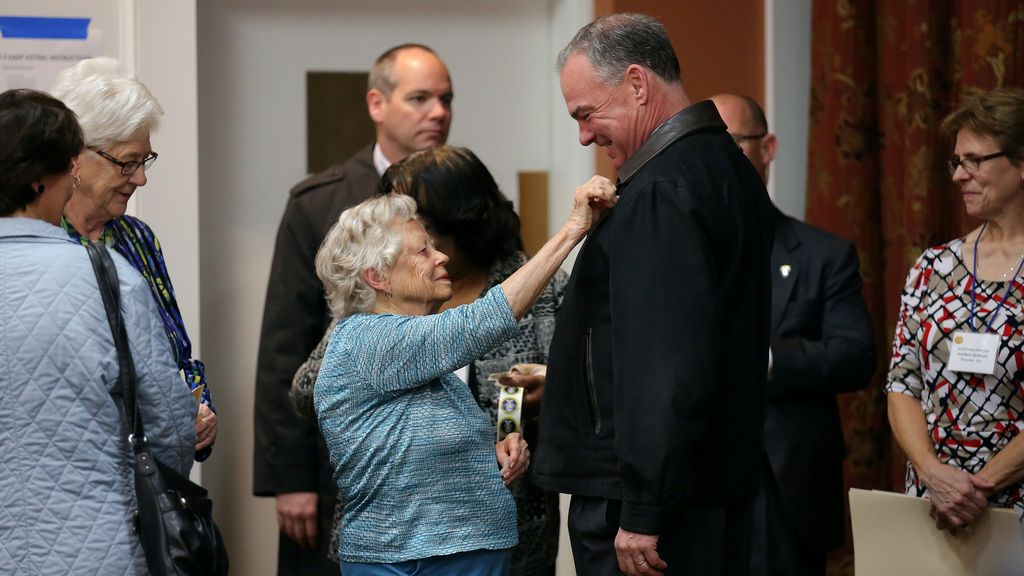 Una mujer pone la pegatina 'Yo voto' a Tim Kaine