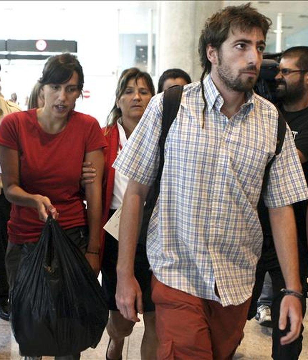 El barcelonés Bernat Palau y la mallorquina Aina Frau, los dos jóvenes supervivientes del accidente en un río mexicano, en el que perdieron la vida tres personas y una cuarta continua desaparecida, a su llegada hoy al aeropuerto de El Prat de Barcelona. EFE