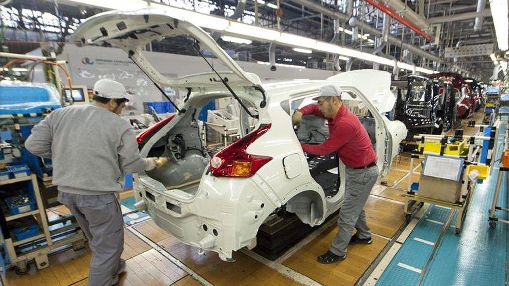 Dos empleados trabajan en una cadena de montaje de Nissan. EFE/Archivo
