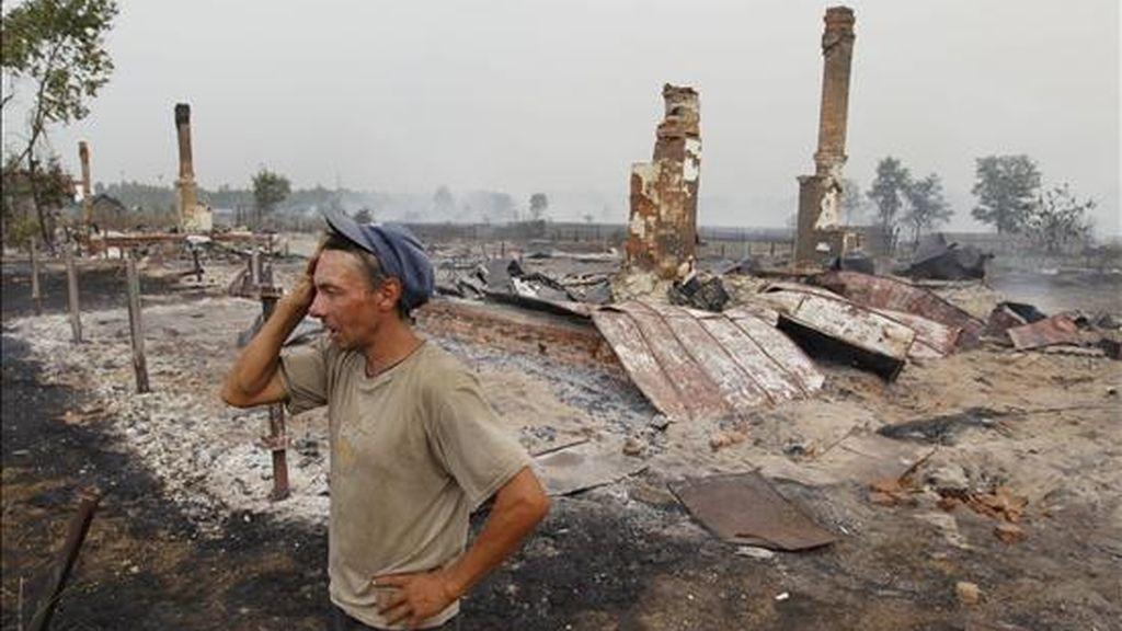 Un hombre junto a su casa quemada por el fuego en la localidad rusa de Mokhovoye, a unos 170 kilómetros de Moscú, este viernes. EFE