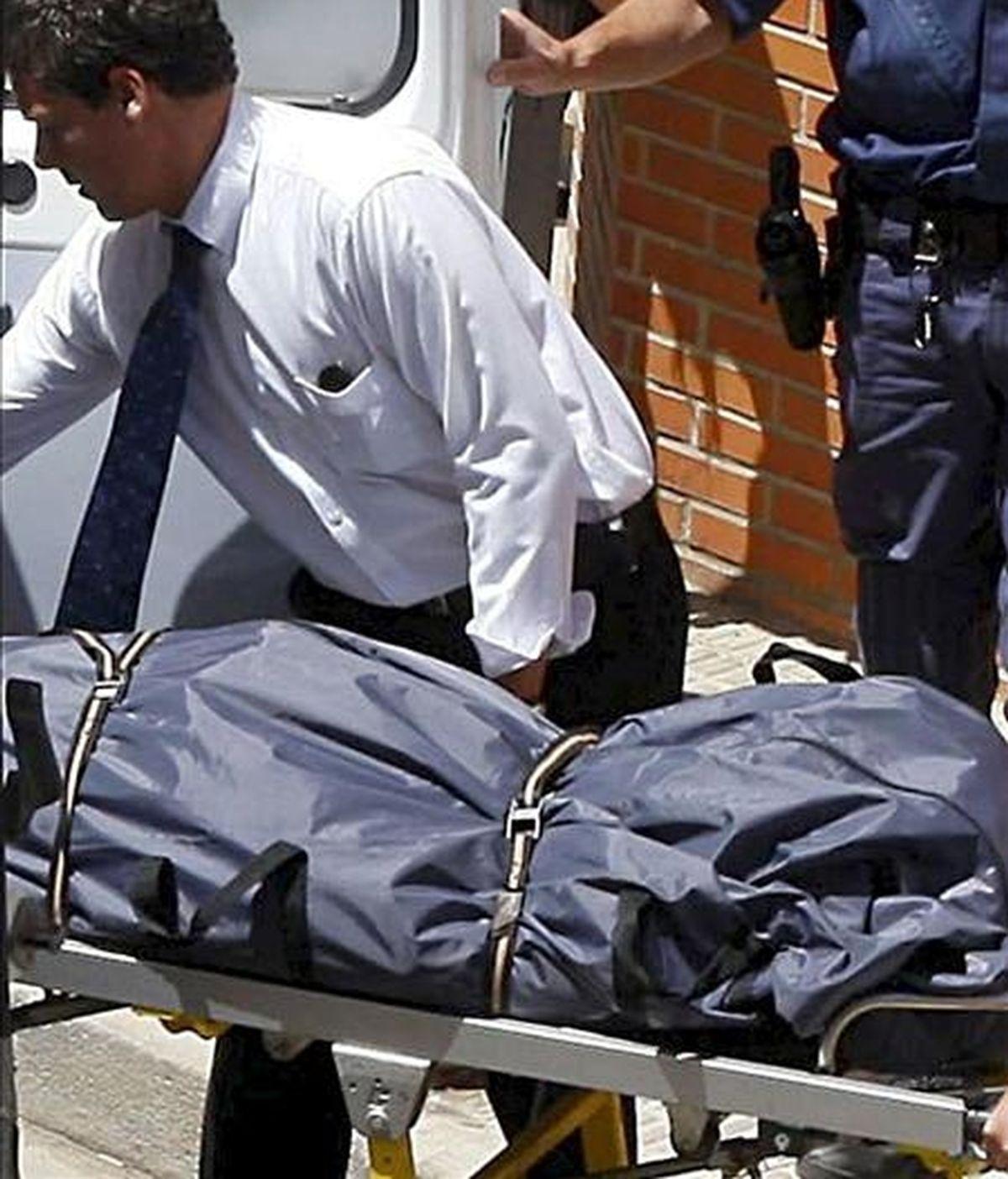 Empleados de los servicios funerarios en el traslado del cadáver de una víctima de violencia machista. EFE/Archivo