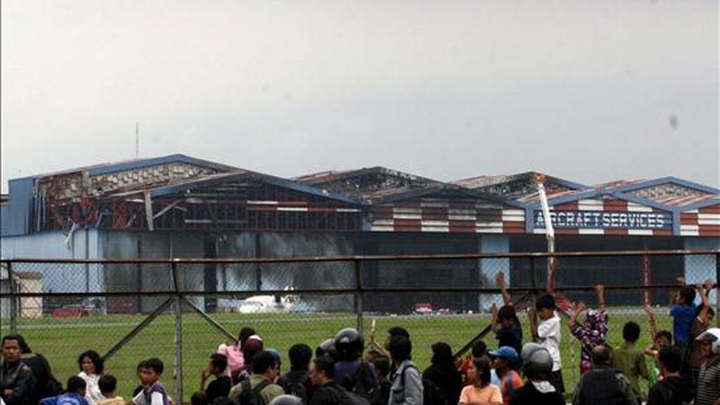 Decenas de personas observan el hangar del aeropuerto Hussein Sastranegara, de Badung, Java (Indonesia), dañado en un accidente aéreo, el 6 de abril de 2009. Al menos 25 personas murieron hoy tras estrellarse un avión militar contra un hangar en una base aérea en el oeste de la isla indonesia de Java, informó el portavoz de la Fuerza Aérea, Bambang Sulistyo. EFE