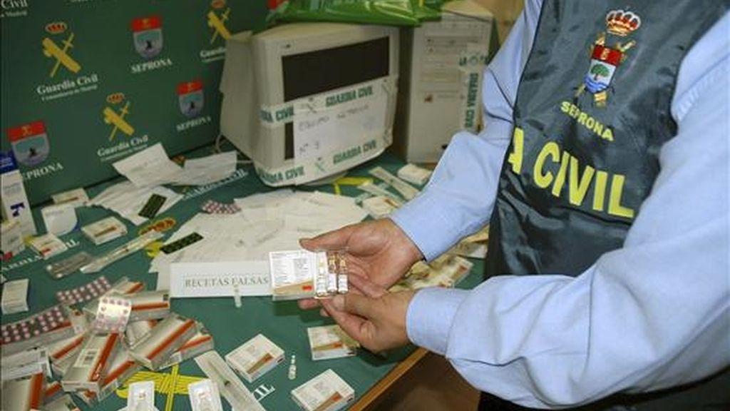 Un agente de la Guardia Civil muestra parte del material incautado en una operación de venta de anabolizantes. EFE/Archivo