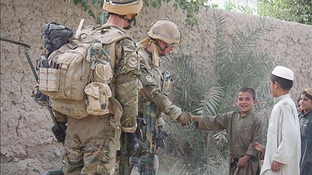 Dos militares de la ISAF (Fuerza Internacional de Asistencia a la Seguridad), conversan con un grupo de menores en Nad e Ali durante la Operación Tor Shezada en Helmand (Afganistán). La operación conjunta del ISAF y el Ejército afgano contra los insurgentes, tendrá lugar desde Sayedebab al sur de Nad E Ali en la provincia de Helmand. EFE/CPL Joe Blogs/Ministerio Británico de Defensa