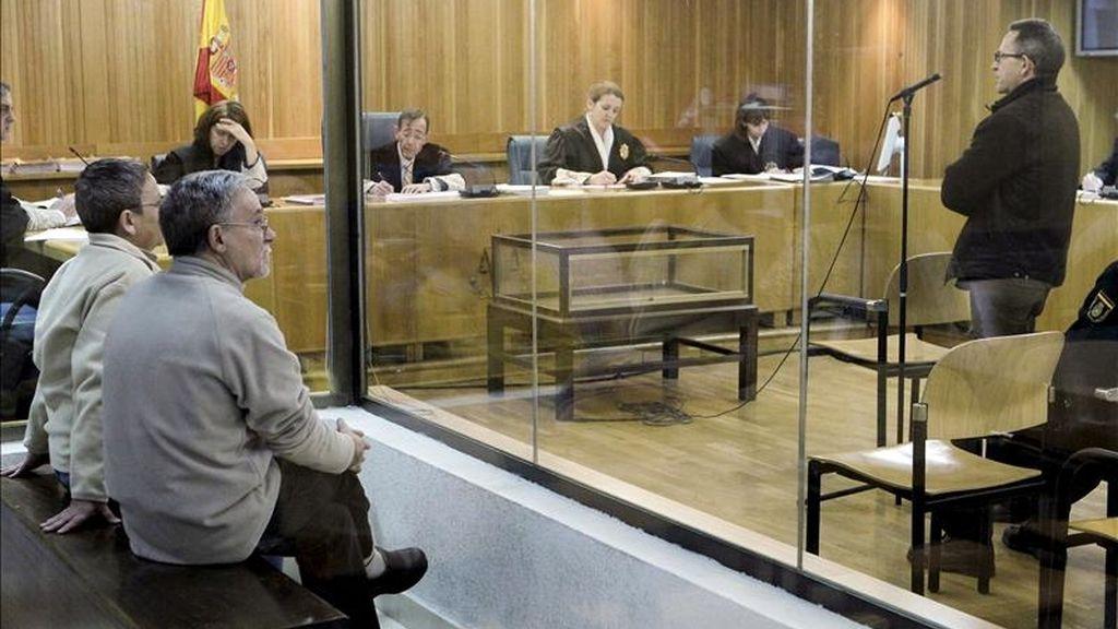 El ex dirigente del GRAPO Fernando Silva Sande (d) presta declaración mientras sus compañeros Manuel Pérez Martínez y Victoria Gómez Méndez (i) permanecen en el banquillo tras una cristalera durante el juicio celebrado hoy en la Audiencia Nacional contra los tres por ordenar la colocación el 1 de junio de 1998 en Madrid de un artefacto explosivo en una empresa de trabajo temporal, hechos por los que la Fiscalía pide para ellos 55 años de prisión. EFE