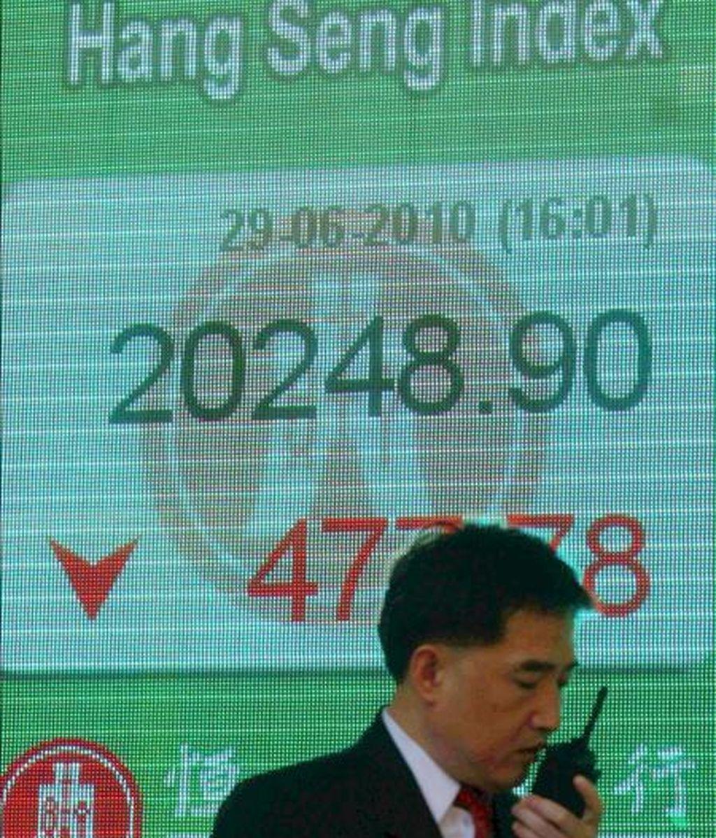 Un hombre pasa delante de un panel electrónico de una sucursal bancaria de Hong Kong (China) que muestra el valor alcanzado por el índice Hang Seng de la Bolsa de Hong Kong. EFE/Archivo