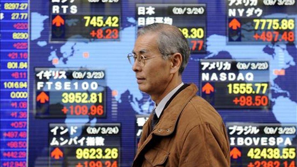 Un hombre pasa por delante de un panel electrónico en el que se muestran los valores de la Bolsa, en Tokio. EFE/Archivo