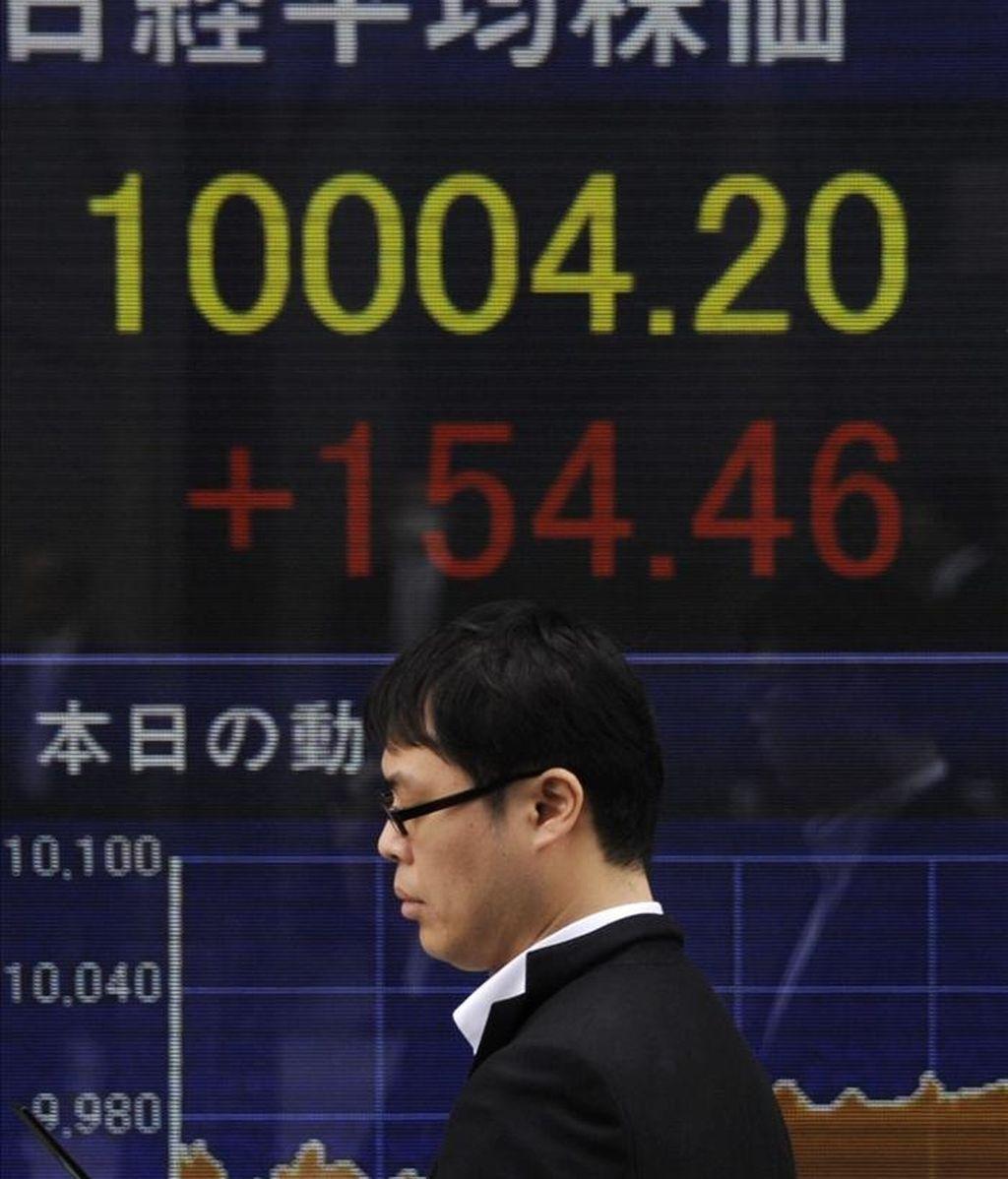 Un hombre camina frente a una pantalla con los indicadores de la bolsa en Tokio. EFE/Archivo