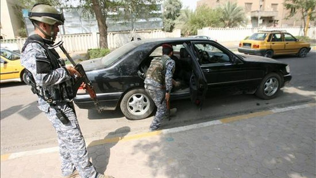 Policías iraquíes inspeccionando un vehículo en un punto de control del centro de Bagdad este martes. EFE