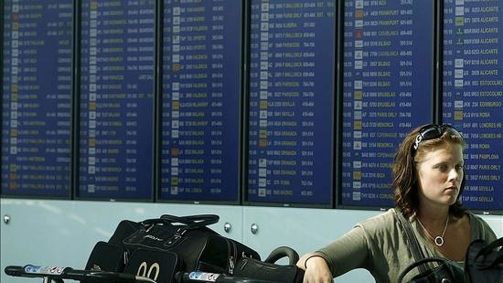 Una pasajera ante un panel de información de la Terminal 1 del aeropuerto de El Prat. EFE